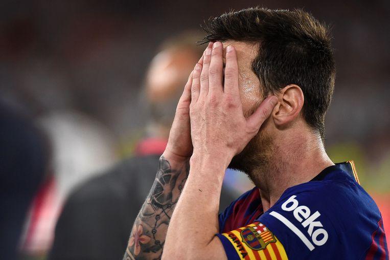 Lionel Messi met de handen voor het gezicht.