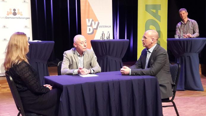 Ad Graumans poogt Anne Cristien Spekle (VVD, links) en Carlo van Esch (PGB) de degens te laten kruisen. Guus Mulders luistert achter zijn hangtafel mee.