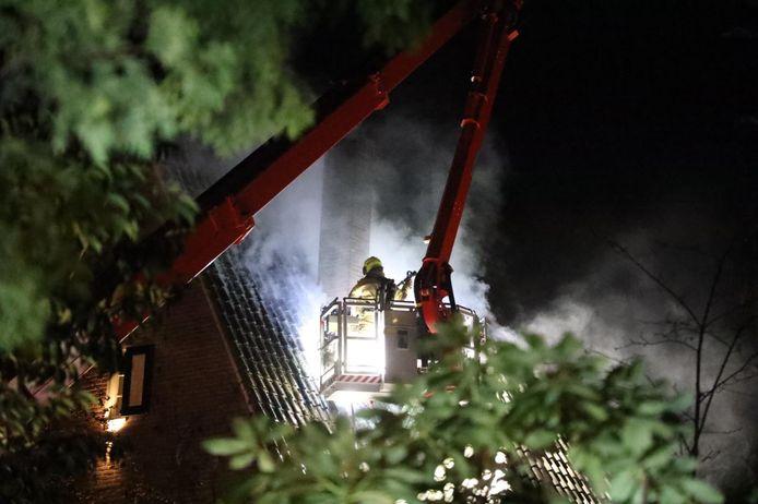 De brandweer probeert de brand in de Arnhemse woning onder controle te krijgen.