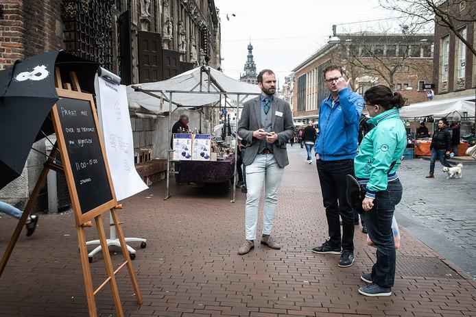 Stadsconferentie op straat: Nijmegenaren Reinier Gal en Iris Pulles in gesprek met een raadslid. Op grote vellen papier konden Nijmegenaren ideeën en wensen kwijt.
