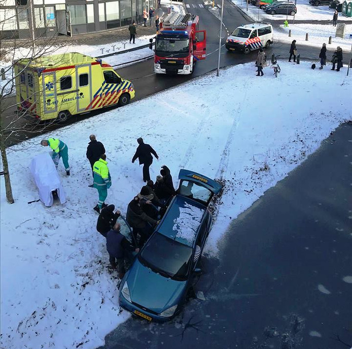 Omstanders zorgden ervoor dat de auto niet verder het water inzakte.