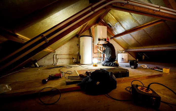 Een erkende installateur is bezig met het installeren van een warmtepomp bij een verwarmingsketel, als onderdeel van een project om een jaren-60 woning energiezuinig te maken.
