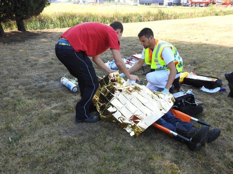 Een van de slachtoffers wordt verzorgd op een grasveld voor het gebouw.
