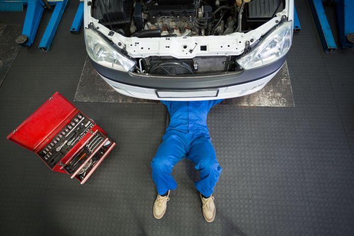 Automonteur liggend onder auto