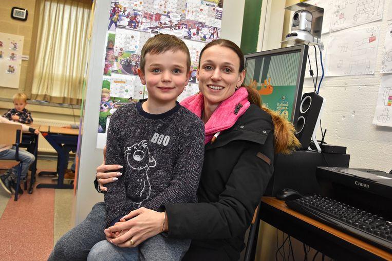 Cas (7) volgt les in De Wijzer via Bednet. Hier poseert hij met zijn mama in klas.