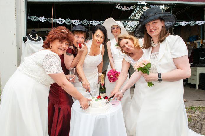 Medewerkers van de kringloopwinkel showen de trouwjurken, die ze dankzij een gulle gever voor 75 euro mogen verkopen.