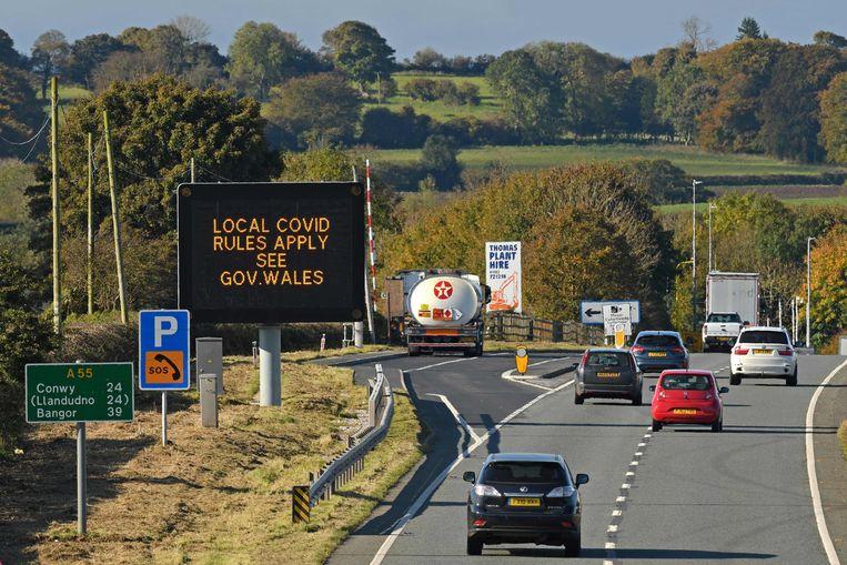 Verkeersborden geven aan dat in Wales vanaf vandaag eigen strenge regels gelden: een complete lockdown. Beeld AFP