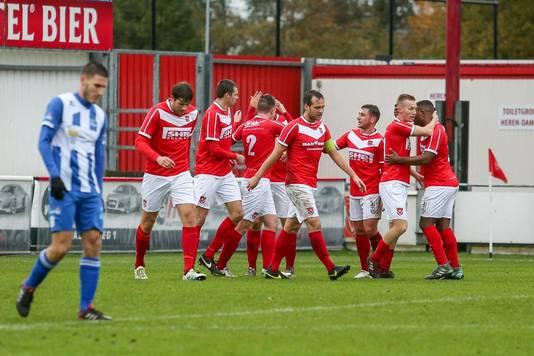 Fabian Wilson loopt met gebogen hoofd, terwijl de spelers van Harkemase Boys op de achtergrond een doelpunt vieren.