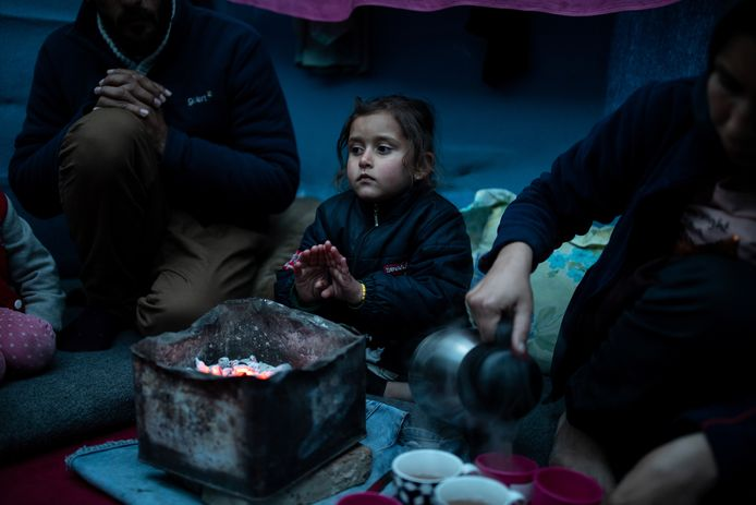 Vluchtelinge Marjan Hosini (3) warmt haar handen aan een geïmproviseerde kolenkachel in vluchtelingenkamp Moria op Lesbos. De vluchtelingen op de Griekse eilanden wonen in erbarmelijke omstandigheden.