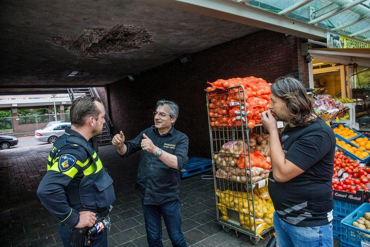 Wijkagent Jeroen van der Schot in gesprek met winkeliers. Beeld Jean-Pierre Jans