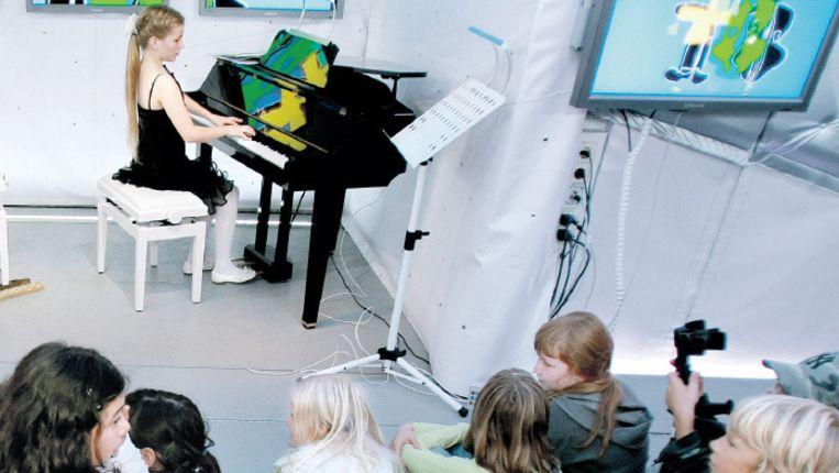 De rijdende concertzaal Classic Express doet een basisschool in Haarlem aan. Kinderen worden getrakteerd op een concert van jonge musici. ©ANP Beeld