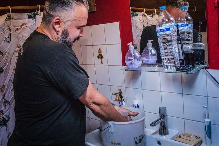 Mark wast zijn handen in emmer in de badkamer. De tanden poetsen ze met flessenwater.