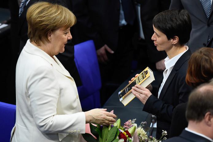 Merkel wordt gefeliciteerd door voormalig AfD-kopstuk Frauke Petry (R).