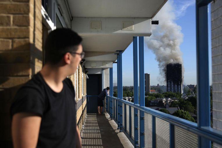 Een bewoner van een flat kijkt naar de brand in Grenfell Tower. Beeld AFP