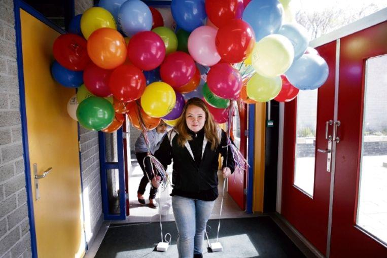 Een leerling van het Vmbo Groen in Nijmegen brengt de ballonnen naar buiten, waaraan scholieren geschreven 'vrijheidsbelevingen' zullen bevestigen, die ze vervolgens laten wegvliegen. (FOTO JÃ¿RGEN CARIS, TROUW) Beeld