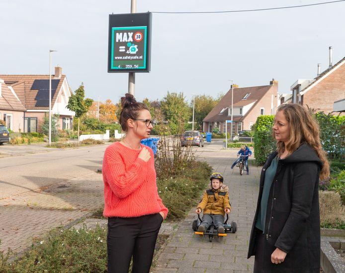 Maartje Bruinenbeg (links) en Miriam Doorn zijn tevreden over de betalende snelheidsmeter die bij hen in de straat hing.