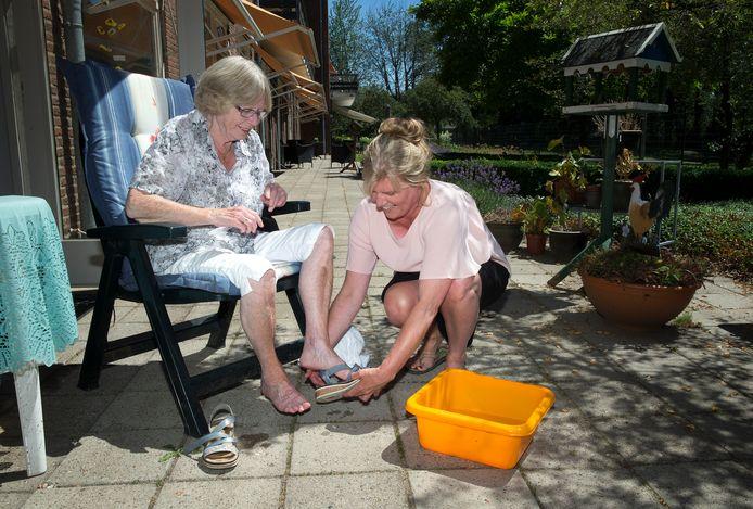 Jo Hartjes krijgt een verkoelend voetenbadje van verpleegkundige Bep Klein Winkel in Den Ooiman.