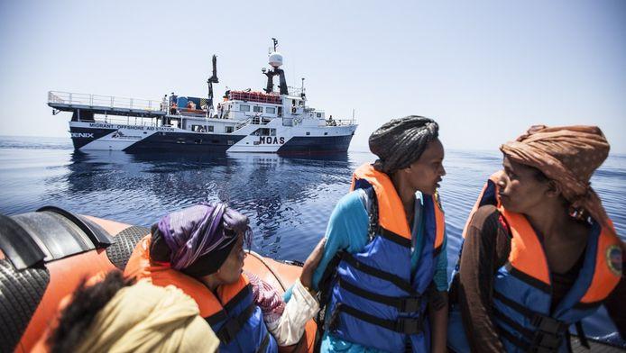 Migranten wachten op redding in een sloep voor de kust van Sicilië.