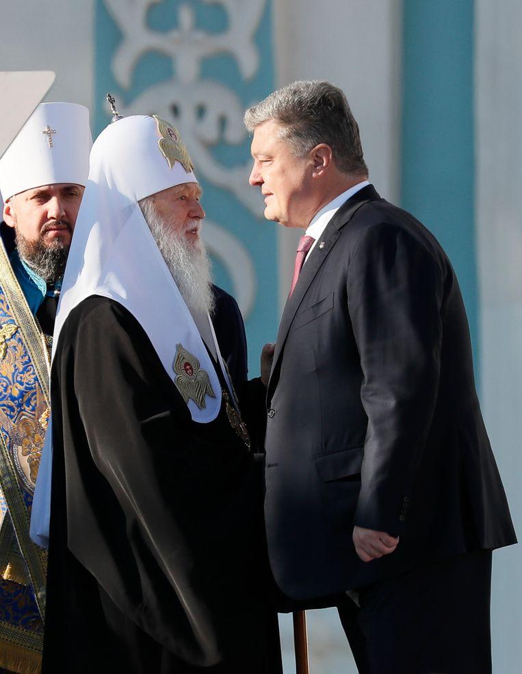 Oekraïense president Petro Porosjenko (R) begroet patriarch Filaret, hoofd van de Oekraïense Orthodoxe Kerk Beeld REUTERS
