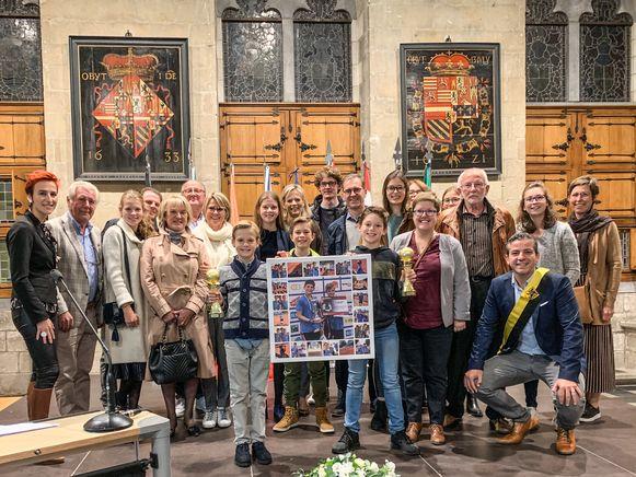 De twee jonge kampioenen, omringd door familie, teamleden van Tennisclub Oudenaarde en een delegatie van het stadsbestuur.