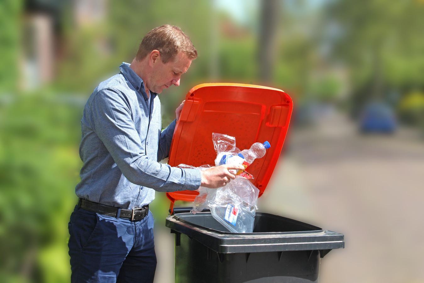 Man gooit plastic afval weg in een PMD-container.