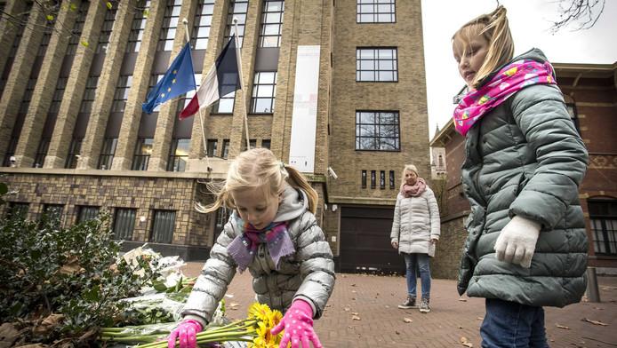 Meisjes leggen bloemen neer bij de Franse ambassade om hun medeleven te betuigen voor de slachtoffers van de aanslagen in Parijs. De ambassade zou niet genoeg beveiligd worden.