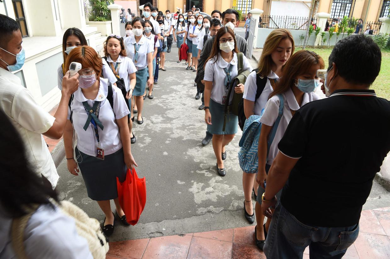 Ook in Manilla, op de Filipijnen, dragen studenten inmiddels mondkapjes. Ook wordt hun temperatuur gecontroleerd. Gisteren dook het virus op in de eilandenstaat, bij een vrouw van 38. Beeld AFP