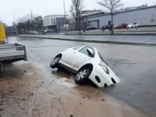 Auto zakt weg in straat na waterleidingbreuk in de Keesomstraat in Ede