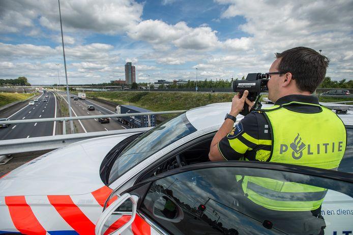 Verkeersagent Merlijn Kuiper met lasergun boven de A16 bij Prinsenbeek.