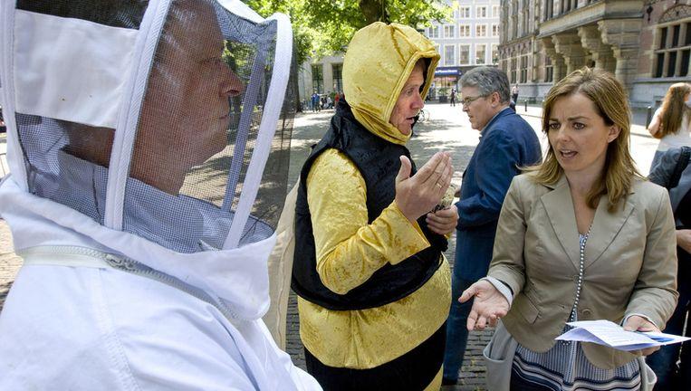 Twee mensen gehuld in een bijenpak en in een imker-uitrusting spreken tijdens een actie met fractievoorzitter van de Partij voor de Dieren Marianne Thieme voor de ingang van de Tweede Kamer in Den Haag. Beeld