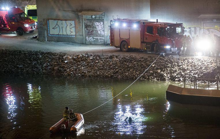 Duikers en reddingswerkers zoeken naar de slachtoffers. Beeld null