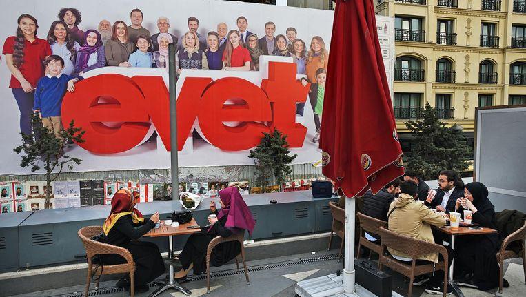 Turken eten bij de Burger King op het Taksimplein. Op de achtergrond een reusachtige poster van de AKP met daarop Evet, Turks voor 'Ja'. Beeld Guus Dubbelman / de Volkskrant