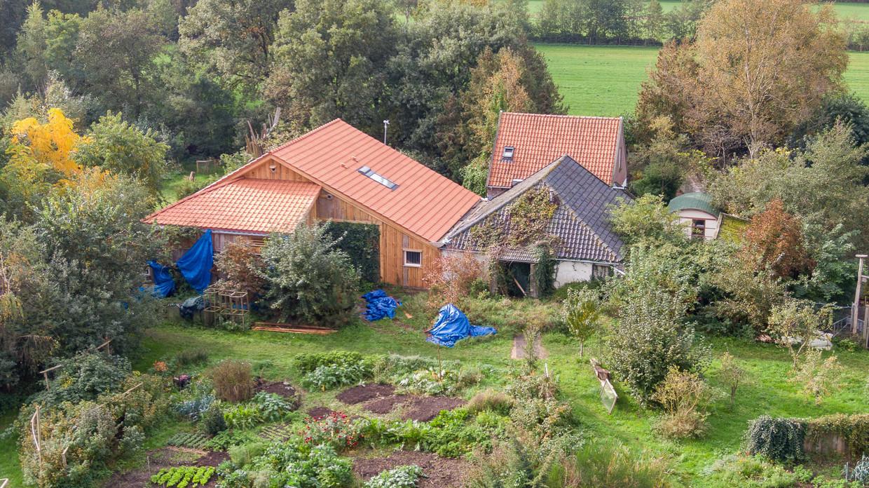 Een dronefoto van de boerderij aan de Buitenhuizerweg in Ruinerwold, waar zes mensen al jaren in de kelder woonden en wachtten op 'het einde der tijden'.