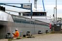 Een man is bezig met het onderhoud van een schip in de haven van Werkendam.