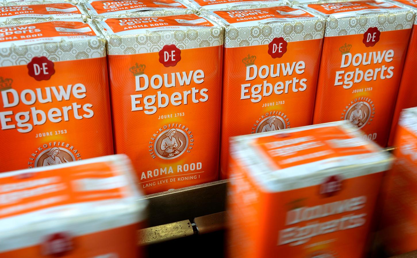 Koffiepakken van Douwe Egberts rollen van de band in de fabriek. De verpakking van Aroma Rood heeft ter gelegenheid van de troonswisseling een oranje kleur gekregen.