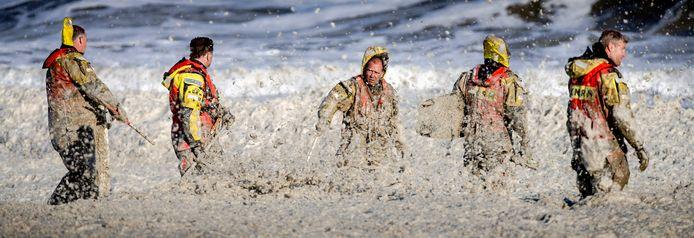 Leden van de KNRM trotseren het opvliegend schuim tijdens de hervatte zoektocht.