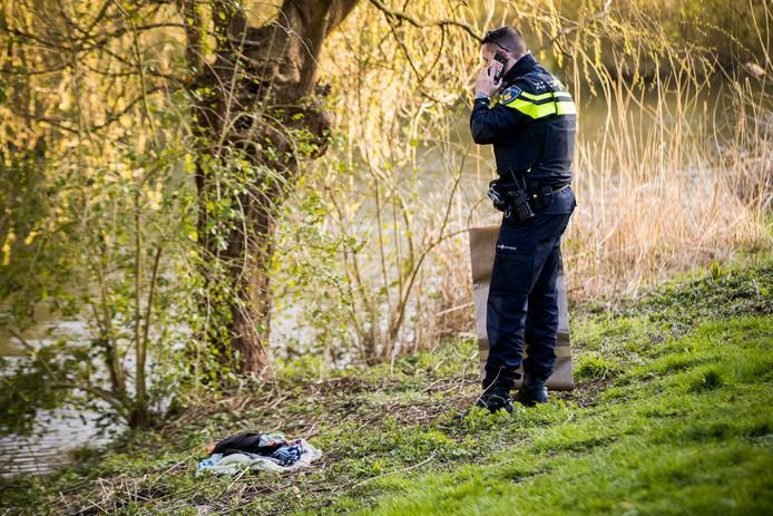 Een politieagent bij het hoopje dameskleding dat langs de Kromme Rijn werd gevonden.