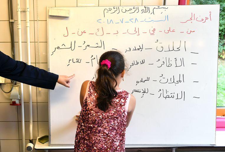 Een meisje bestudeert Arabische tekst op een whuit. Beeld Marcel van den Bergh