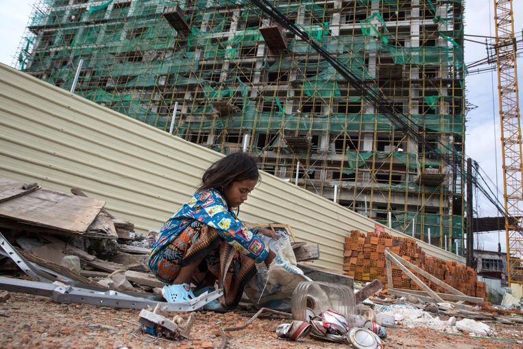 Een Cambodjaans meisje verzamelt blikjes en ander metaal op een bouwlocatie waar kantoren en appartementen voor Chinezen worden neergezet. Veel Cambodjanen leven in armoede.   Beeld Paula Bronstein / Getty