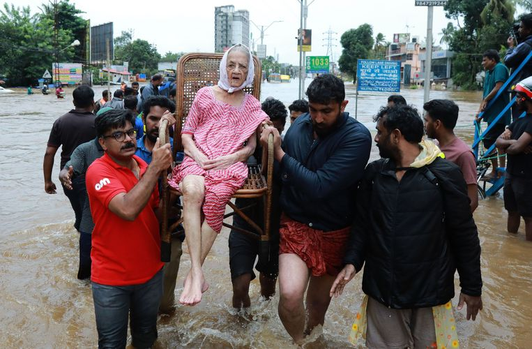 Een oudere vrouw wordt geëvacueerd uit een woonwijk in de door overstromingen getroffen deelstaat Kerala. Beeld AFP