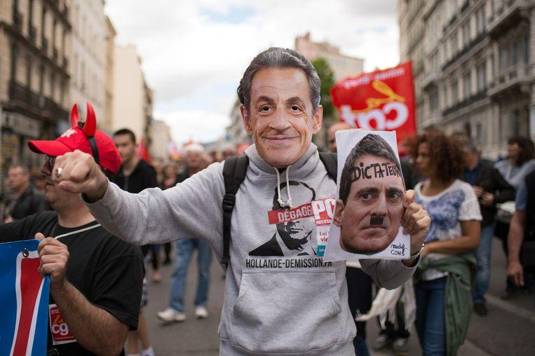 Een demonstrant met een masker van Sarkozy houdt een foto van Manuel Valls vast tijdens een protest in Marseille. Beeld afp