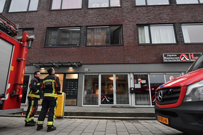 Brandweermannen kijken naar het appartement met waterschade boven Hachi in Alphen