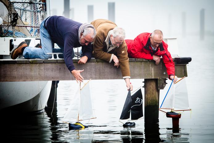 Voorzitter Van Dam, penningmeester Rob Mooij en clublid Mar Augustijn laten hun klomp met zeiltje voor het eerst te water.