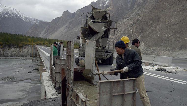 Chinese arbeiders werken in Noord-Pakistan aan de Karakoram Highway. De snelweg moet tot meer handel en stabiliteit leiden in China's 'Wilde Westen'. Beeld AFP/Getty Images