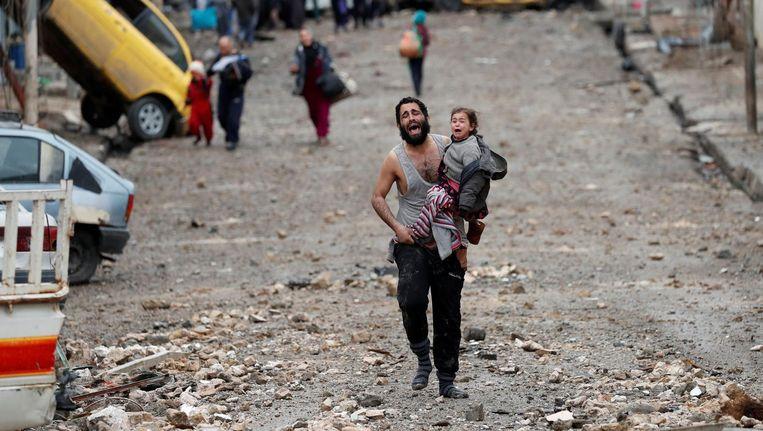 Huilend draagt een man zijn dochter vanuit IS-gebied naar het door het leger bevrijdde gebied van Mosul. Beeld reuters