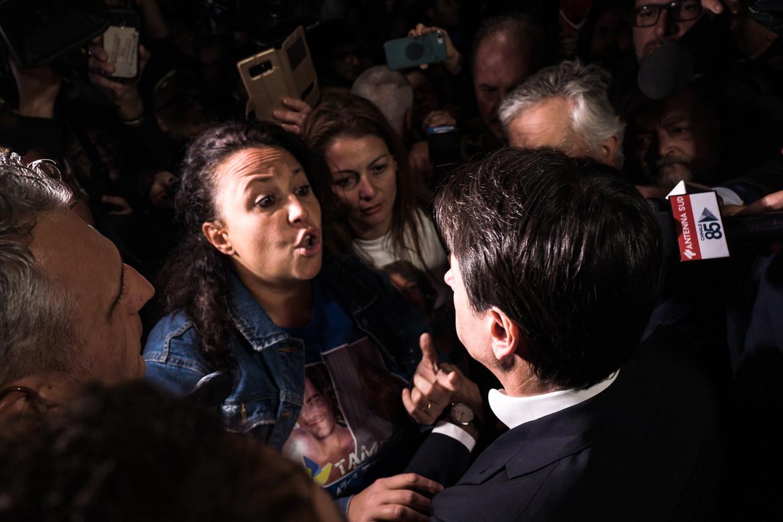 Een vrouw die haar man en vader is verloren doet bij de staalfabriek haar beklag tegenover premier Conte.