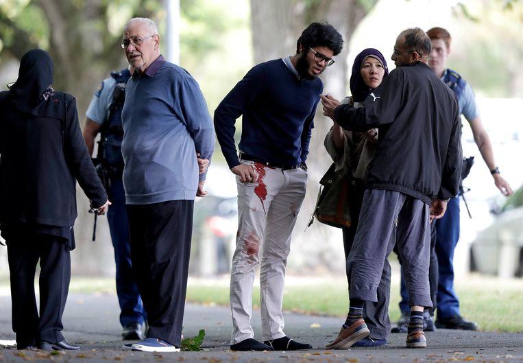 Omstanders bij de moskee waar Tarrant zijn bloedbad aanrichtte.  Beeld AP