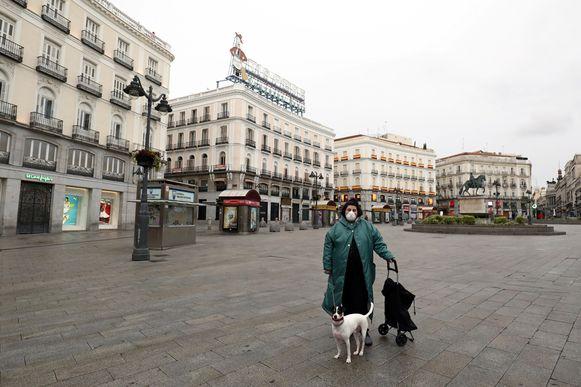 Een vrouw op het verlaten Puerta del Sol-plein in Madrid.