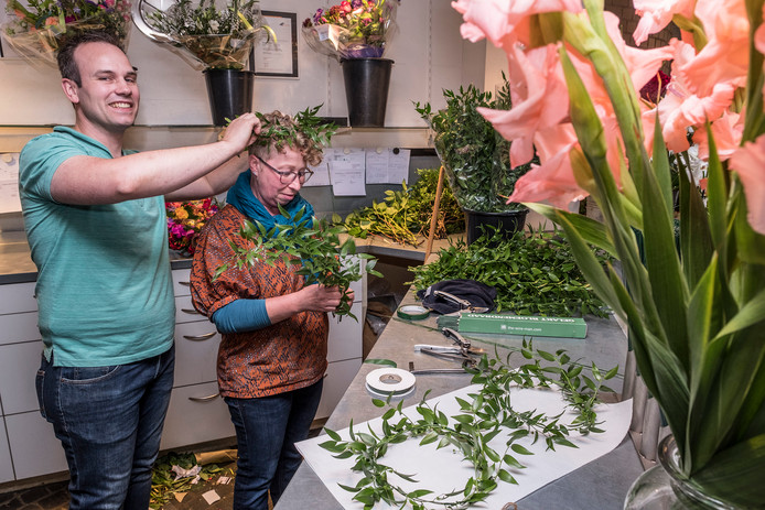 Mede-eigenaar Roel van Hoof van Bloemsierkunst Wilhelmientje zet alvast een Vierdaagse-lauwerkrans op het hoofd van medewerkster Ursula.