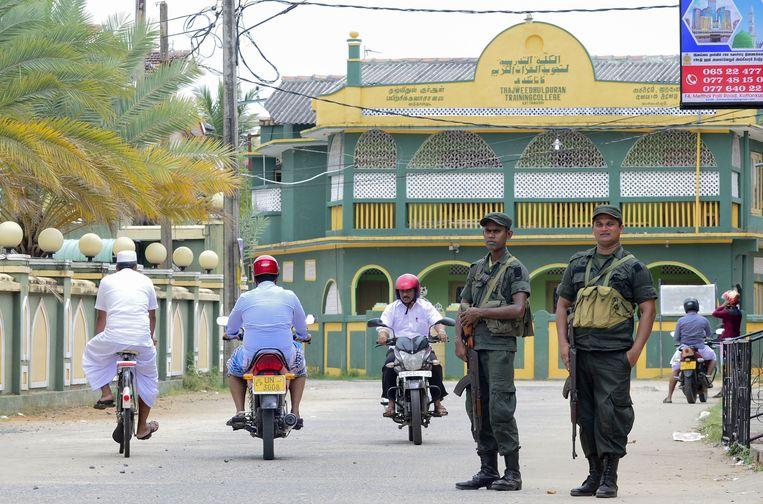 Militairen op straat bij de Grand Jumma Moskee in Kattankudy.  Beeld AFP